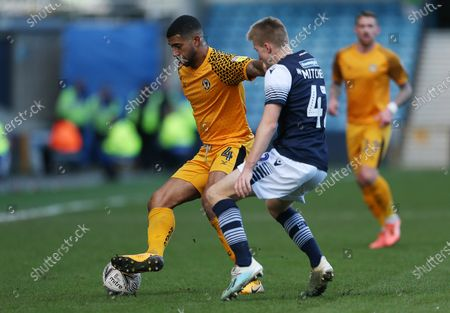 Joss Labadie of Newport County is challenged by Billy Mitchell of Millwall.