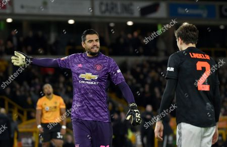 Manchester United's goalkeeper Sergio Romero, left, speaks with Manchester United's Victor Lindelof during the English FA Cup third round soccer match between Wolverhampton Wanderers and Manchester United at the Molineux Stadium in Wolverhampton, England