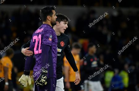 Manchester United's goalkeeper Sergio Romero, left, and Manchester United's Victor Lindelof walk on the pitch at the end of the English FA Cup third round soccer match between Wolverhampton Wanderers and Manchester United at the Molineux Stadium in Wolverhampton, England