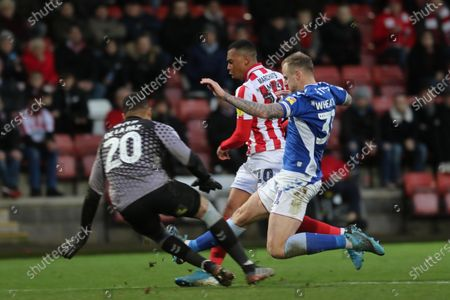 Tahvon Campbell gets past David Wheater to shoot, but it is saved by Zeus do la Paz during the EFL Sky Bet League 2 match between Cheltenham Town and Oldham Athletic at Jonny Rocks Stadium, Cheltenham