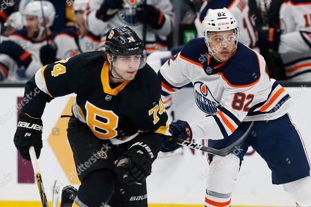 Boston Bruins' Jake DeBrusk (74) and Edmonton Oilers' Caleb Jones (82) battle during the first period on an NHL hockey game in Boston