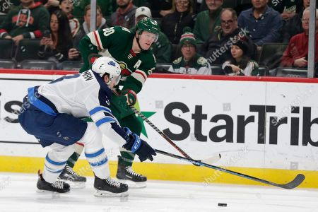 Minnesota Wild defenseman Ryan Suter (20) shoots with pressure from Winnipeg Jets defenseman Tucker Poolman (3) in the first period of an NHL hockey game, in St. Paul, Minn. The Wild defeated the Jets 3-2