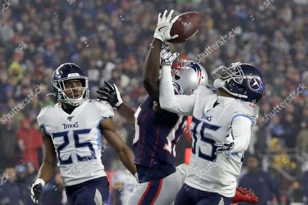 Tennessee Titans defensive back Tramaine Brock (35) breaks up a pass to New England Patriots wide receiver Phillip Dorsett as Titans cornerback Adoree' Jackson (25) looks on during an NFL wild-card playoff football game, in Foxborough, Mass