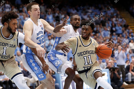 Georgia Tech guard Bubba Parham (11) drives to the basket while North Carolina guardsJustin Pierce (32) and Brandon Robinson defend during the second half of an NCAA college basketball game in Chapel Hill, N.C., . Georgia Tech forward James Banks III is at left