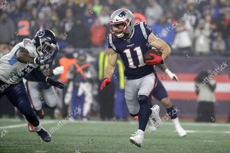 New England Patriots wide receiver Julian Edelman carries the ball as Tennessee Titans linebacker David Long, left, chases in the second half of an NFL wild-card playoff football game, in Foxborough, Mass