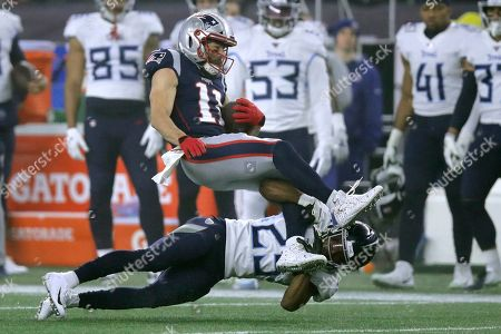 Tennessee Titans cornerback Adoree' Jackson, below, tackles New England Patriots wide receiver Julian Edelman in the first half of an NFL wild-card playoff football game, in Foxborough, Mass