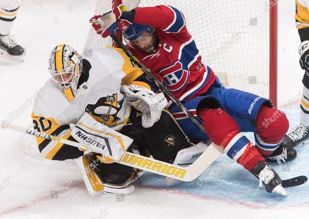 Montreal Canadiens captain Shea Weber collides with Pittsburgh Penguins goaltender Matt Murray during the first period of an NHL hockey game, in Montreal