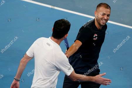 Daniel Evans of Britain shakes hands with team coach Tim Henman after winning his match in his game against David Goffin of Belgium during their ATP Cup tennis match in Sydney