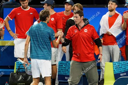 Russia's Daniil Medvedev, left, is congratulated by Russian Captain Marat Safin after defeating John Isner of the United State in their match at the ATP Cup in Perth, Australia