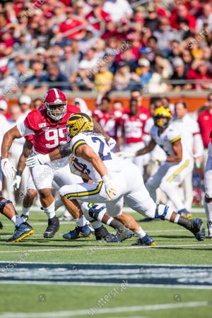 Alabama defensive end Raekwon Davis (99) focuses on Michigan running back Zach Charbonnet (24) during Vrbo Citrus Bowl game action between the Michigan Wolverines and the Alabama Crimson Tide at Camping World Stadium in Orlando, Florida