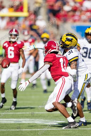 Alabama wide receiver Henry Ruggs III (11) and Michigan cornerback Vincent Gray (31) fight for the pass during Vrbo Citrus Bowl game action between the Michigan Wolverines and the Alabama Crimson Tide at Camping World Stadium in Orlando, Florida