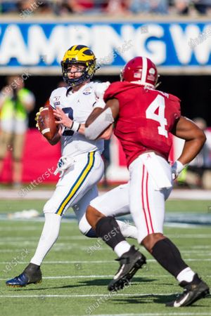 Stock Photo of Michigan quarterback Shea Patterson (2) looks to pass around Alabama linebacker Christopher Allen (4) during Vrbo Citrus Bowl game action between the Michigan Wolverines and the Alabama Crimson Tide at Camping World Stadium in Orlando, Florida