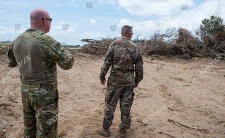 Stock Image of Feb. 24, 2018 and released by the U.S. Air Force, U.S. Air Force Lt. Col. Vance Goodfellow, left, 475th Expeditionary Air Base Squadron (EABS) commander, and U.S. Army Lt. Col. Todd Martin, safety officer assigned to the Combined Joint Task Force - Horn of Africa (CJTF-HOA) Safety directorate, look at trees that are being cleared during a battlefield circulation site visit at Camp Simba, Manda Bay, Kenya. The al-Shabab extremist group said that it has attacked the Camp Simba military base used by U.S. and Kenyan troops in coastal Kenya, while Kenya's military says the attempted pre-dawn breach was repulsed and at least four attackers were killed