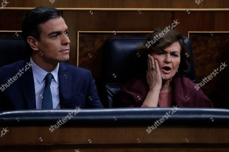 Spain's caretaker deputy Prime Minister Carmen Calvo Poyato, right, gestures next to Spain's interim Prime Minister Pedro Sanchez while looking towards the Popular party members at the Spanish Parliament in Madrid, Spain,. Spain's interim Prime Minister Pedro Sanchez is facing the first of two opportunities Sunday to win the endorsement of the Spanish Parliament to form a left-wing coalition government. It would be Spain's first coalition government since the return of democracy following the death of dictator Francisco Franco in 1975