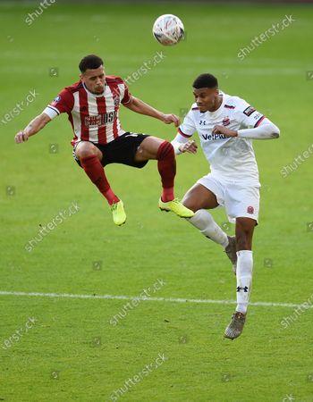 Kyle Jameson of AFC Fylde challenges Ravel Morrison of Sheffield United.