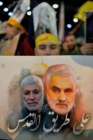 Supporters of Hezbollah carry pictures of the Iranian Revolutionary Guards Corps (IRGC) Lieutenant general and commander of the Quds Force Qasem Soleimani the words reads in Arabic 'On the road to Quds' as they listen to Hezbollah's Secretary-General Sayed Hassan Nasrallah during his mass rally in the southern suburb of Beirut, Lebanon, 05 January 2020. The US Pentagon announced that Iran's Quds Force leader Soleimani and Iraqi militia commander Abu Mahdi al-Muhandis were killed on 03 January 2020 following a US airstrike at Baghdad's international airport. The attack comes amid escalating tensions between Tehran and Washington.