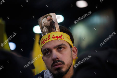 """A supporter of Hezbollah leader Hassan Nasrallah wears a headband that reads, """"death to America,"""" and a picture of slain Iranian Revolutionary Guard Gen. Qassem Soleimani as he waits for a televised speech in a southern suburb of Beirut, Lebanon, following the U.S. airstrike in Iraq that killed Soleimani. Nasrallah called the killing of Soleimani a """"clear, blatant crime"""" that will transform the Middle East"""
