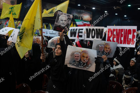 """Stock Photo of Supporters of Hezbollah leader Hassan Nasrallah wave flags and placards that say """"we vow revenge,"""" ahead of the leader's televised speech in a southern suburb of Beirut, Lebanon, following the U.S. airstrike in Iraq that killed Iranian Revolutionary Guard Gen. Qassem Soleimani. The placard in the foreground depicts Soleimaini and Iraq's Popular Mobilization forces commander Abu Mahdi al-Muhandis, who was also killed in the strike. Arabic reads: """"On the road to Jerusalem"""
