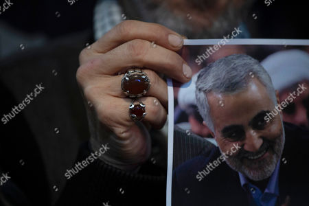 Stock Picture of A supporter of Hezbollah leader Hassan Nasrallah holds a portrait of killed Iranian Revolutionary Guard Gen. Qassem Soleimani ahead of the leader's televised speech in a southern suburb of Beirut, Lebanon, following the U.S. airstrike in Iraq that Soleimani