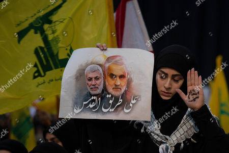 """A supporter of Hezbollah leader Sayyed Hassan Nasrallah wears the words """"powerful revenge, on her hand, ahead of the leader's televised speech in a southern suburb of Beirut, Lebanon, following the U.S. airstrike in Iraq that killed Iranian Revolutionary Guard Gen. Qassem Soleimani. The placard in depicts Soleimaini and Iraq's Popular Mobilization forces commander Abu Mahdi al-Muhandis, who was also killed in the strike. Arabic reads: """"On the road to Jerusalem"""