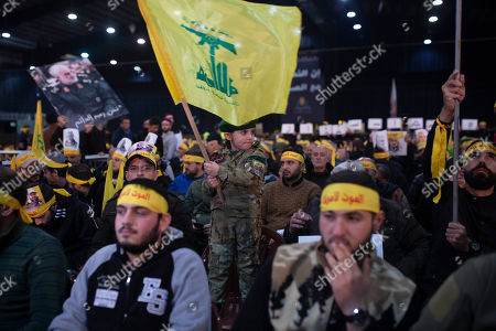 A child in tiny military fatigues waves the Hezbollah flag as supporters of the group's leader Sayyed Hassan Nasrallah wait for his televised speech in a southern suburb of Beirut, Lebanon, following the U.S. airstrike in Iraq that killed Iranian Revolutionary Guard Gen. Qassem Soleimani