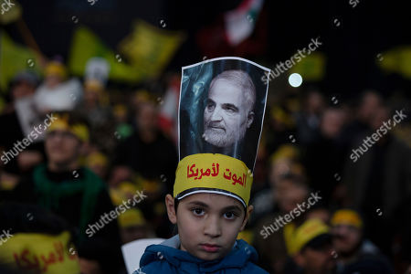 """Stock Image of A child wears a picture of slain Iranian Revolutionary Guard Gen. Qassem Soleimani as supporters of Hezbollah leader Sayyed Hassan Nasrallah gather for his televised speech in a southern suburb of Beirut, Lebanon, following the U.S. airstrike in Iraq that killed Soleimani. The headband reads, """"death to America"""