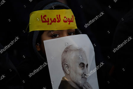 """Stock Picture of A child peeks from behind a picture of slain Iranian Revolutionary Guard Gen. Qassem Soleimani as supporters of Hezbollah leader Sayyed Hassan Nasrallah gather for his televised speech in a southern suburb of Beirut, Lebanon, following the U.S. airstrike in Iraq that killed Soleimani. The headband reads, """"death to America"""