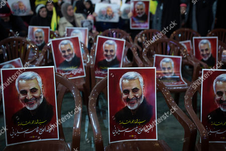 """Posters of slain Iranian Revolutionary Guard Gen. Qassem Soleimani are placed on chairs as supporters of Hezbollah leader Sayyed Hassan Nasrallah gather for his televised speech in a southern suburb of Beirut, Lebanon, following the U.S. airstrike in Iraq that killed Soleimani. The posters read: """"Sayyad of martyrs in the axis of resistance. The martyr Hajj Qassem Soleimani"""