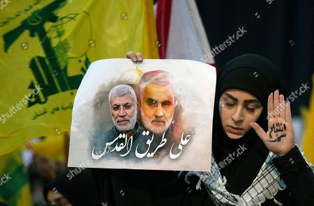 """A supporter of Hezbollah leader Sayyed Hassan Nasrallah wears the words """"powerful revenge"""" on her hand, ahead of the leader's televised speech in a southern suburb of Beirut, Lebanon, following the U.S. airstrike in Iraq that killed Iranian Revolutionary Guard Gen. Qassem Soleimani. The placard in her other hand depicts Soleimaini and Iraq's Popular Mobilization forces commander Abu Mahdi al-Muhandis, who was also killed in the strike. Arabic on placard reads: """"On the road to Jerusalem"""