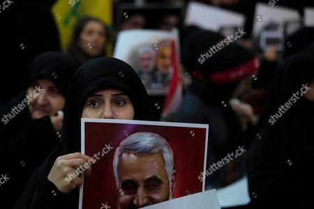 A woman supporter of Hezbollah leader Sayyed Hassan Nasrallah holds a portrait of slain Iranian Revolutionary Guard Gen. Qassem Soleimani before a televised speech by Nasrallah in a southern suburb of Beirut, Lebanon, following the U.S. airstrike in Iraq that killed Soleimani