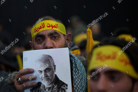 """A supporter of Hezbollah leader Sayyed Hassan Nasrallah holds a portrait of slain Iranian Revolutionary Guard Gen. Qassem Soleimani before a televised speech by Nasrallah in a southern suburb of Beirut, Lebanon, following the U.S. airstrike in Iraq that killed Soleimani. His headband reads: """"death to America"""