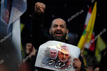 """A supporter of Hezbollah leader Sayyed Hassan Nasrallah chants slogans before his televised speech in a southern suburb of Beirut, Lebanon, following the U.S. airstrike in Iraq that killed Iranian Revolutionary Guard Gen. Qassem Soleimani. The placard in depicts Soleimaini and Iraq's Popular Mobilization forces commander Abu Mahdi al-Muhandis, who was also killed in the strike. Arabic reads: """"On the road to Jerusalem"""