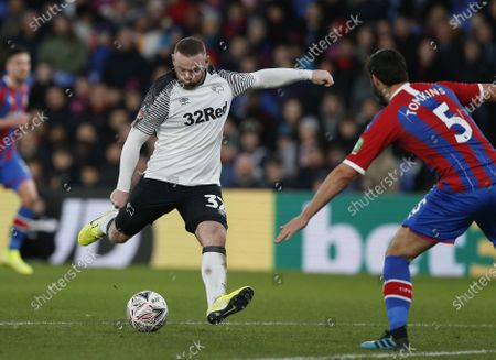 Wayne Rooney of Derby County shoots as James Tomkins of Crystal Palace attempts to block