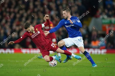 Liverpool's Adam Lallana, left, challenges for the ball with Everton's Gylfi Sigurdsson during the English FA Cup third round soccer match between Liverpool and Everton at Anfield stadium in Liverpool, England