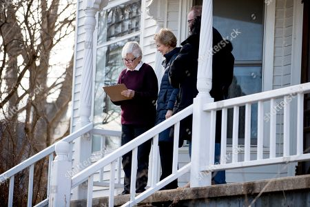 Democratic presidential candidate Sen. Elizabeth Warren, D-Mass., center, accompanied by Jackson County Democratic chair Donna Duvall, gets an undecided caucus goer to sign up with her as she knocks on doors, in Maquoketa, Iowa