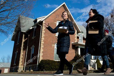 Elizabeth Warren, Donna Duvall. Democratic presidential candidate Sen. Elizabeth Warren, D-Mass., center, accompanied by Jackson County Democratic Party chair Donna Duvall, right, knocks on doors to speak to undecided caucus goers, in Maquoketa, Iowa