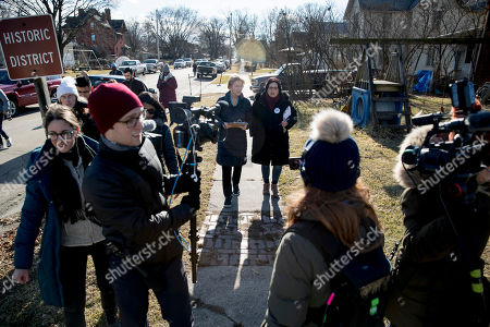 Elizabeth Warren, Donna Duvall. Members of the media surround Democratic presidential candidate Sen. Elizabeth Warren, D-Mass., center left, accompanied by Jackson County Democratic Party chair Donna Duvall, center right, as she knocks on doors to speak to undecided caucus goers, in Maquoketa, Iowa