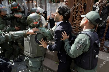 Stock Picture of The opposition deputy Renzo Prieto struggles with members of the Bolivarian National Guard (GNB) while trying to access the headquarters of the National Assembly in Caracas, Venezuela, 05 January 2020. Chavista deputies of the National Assembly (AN, Parliament) elected Luis Parra, former member of the First Justice party, as President of the Parliament, in a brief debate that opposition leader and now former president of the Parliament Juan Guaido did not attend as he was held for hours by the Police around the Legislative Palace. Before the session, troops of the Bolivarian National Police (GNP) and the Bolivarian National Guard (GNB, militarized police), prevented Guaido and other deputies access to Parliament.