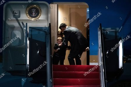 A Secret Service agent stops Theodore James Kushner, front, and his brother Joseph Frederick Kushner, the sons of Ivanka Trump, from exiting Air Force One, at Andrews Air Force Base, Md., following a trip from Trump's Mar-a-Lago estate