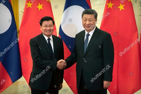 Thongloun Sisoulith, Xi Jinping. Laos' Prime Minister Thongloun Sisoulith, left, and Chinese President Xi Jinping shake hands before a meeting at the Great Hall of the People in Beijing