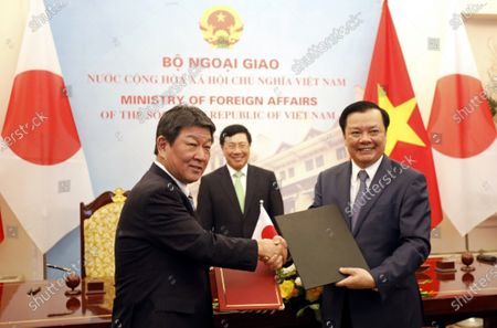 Japan's Foreign Minister Toshimitsu Motegi (L) and Vietnam's Finance Minister Dinh Tien Dung (R) exchange an agreement for waste water treatment of Halong city, as Vietnam's Deputy Prime Minister and Foreign Minister Pham Binh Minh (C) looks on at the Government Guesthouse in Hanoi, Vietnam  06 January 2020.