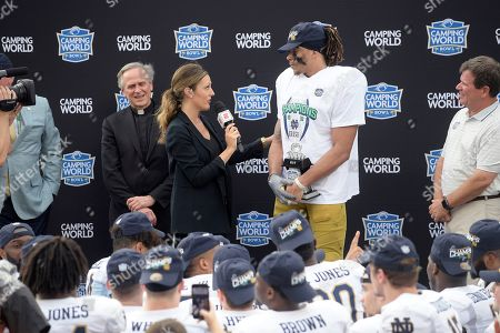 Television sideline reporter Allison Williams, second from left, interviews Notre Dame wide receiver Chase Claypool after receiving the Most Valuable Player trophy after the Camping World Bowl NCAA college football game against Iowa State, in Orlando, Fla