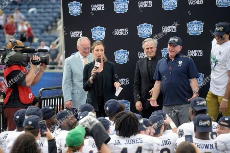 Television sideline reporter Allison Williams, second from left, addresses the crowd before interviewing Notre Dame wide receiver Chase Claypool, right, and head coach Brian Kelly, second from right, after the Camping World Bowl NCAA college football game against Iowa State, in Orlando, Fla