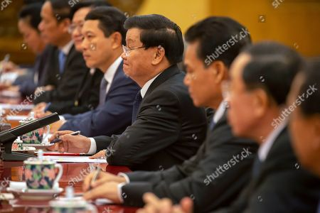 Laos' Prime Minister Thongloun Sisoulith, center, listens as Chinese President Xi Jinping speaks during a meeting at the Great Hall of the People in Beijing