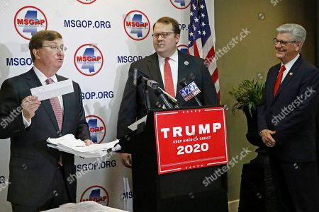Stock Picture of Tate Reeves, Phil Bryant, Lucien Smith. Lt. Gov. Tate Reeves, left, jokes about the check that he will present Mississippi Republican Party Chairman Lucien Smith, center, as part of the ballot access documents he will present on behalf of President Donald J. Trump's campaign, thus enabling him to appear on the party ballot this November, in Jackson, Miss
