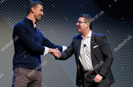 Michael Moskowitz, CEO of Panasonic Corporation of North America, right, shakes hand with Michael Phelps during a Panasonic news conference before the CES tech show, in Las Vegas