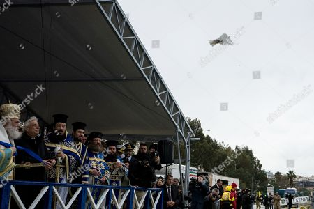 President of the Greek Republic, Prokopis Pavlopoulos releases a white pigeon during the Epiphany day celebration.