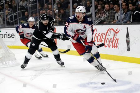 Columbus Blue Jackets' Boone Jenner, right, is defended by Los Angeles Kings' Drew Doughty, center, during the first period of an NHL hockey game, in Los Angeles