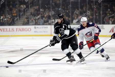 Los Angeles Kings' Drew Doughty, left, controls the puck in front of Columbus Blue Jackets' Riley Nash during the second period of an NHL hockey game, in Los Angeles