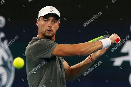 Dimitar Kuzmanov of Bulgaria plays a shot against Steve Darcis of Belgium during their ATP Cup tennis match in Sydney